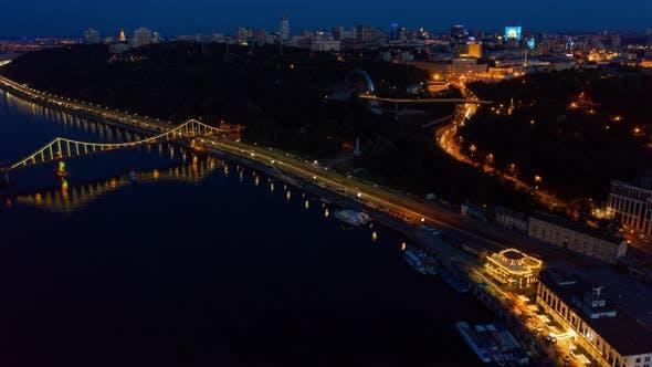Night Kiev Hyperlapse. Colorful Pedestrian Bridge on the Banks of the Dnieper. Aerial Footage