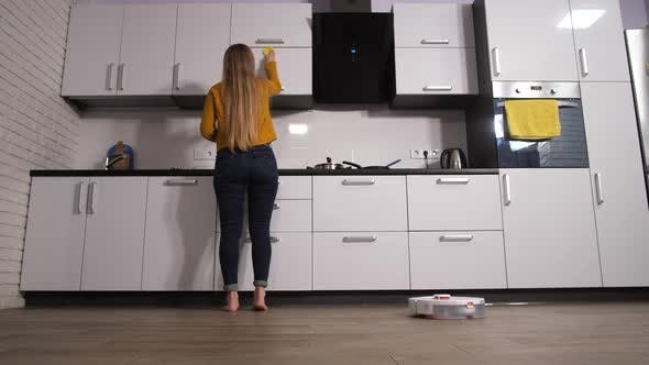 Woman Busy in Kitchen While As Cleaner Works