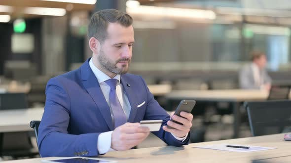 Thumbnail for Middle Aged Businessman Excited By Online Shopping Success on Smartphone