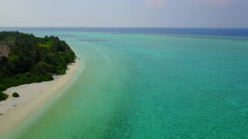 Tropical aerial travel shot of a paradise sunny white sand beach and turquoise sea background in 4K