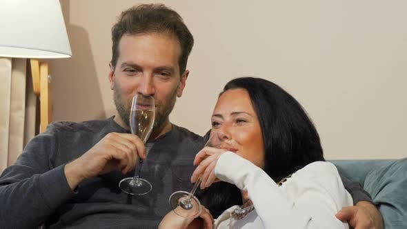 Thumbnail for Happy Mature Couple Laughing Drinking Champagne While Cuddling at Home