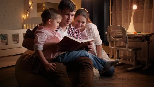 Happy Family with Little Boy Reading Book at Night Before Going To Sleep
