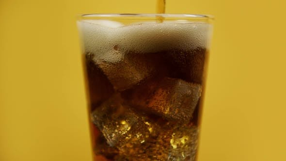 Thumbnail for Pouring Cola Fizzy Drink. Glass Full of Cold Sparkling Soda with Ice Cubes on Yellow Background