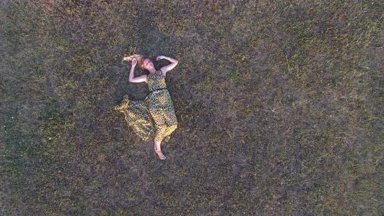 Beautiful woman lying in grass and enjoying