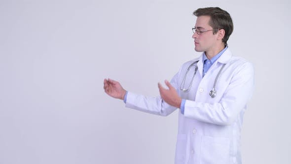 Thumbnail for Young Happy Handsome Man Doctor Showing Something
