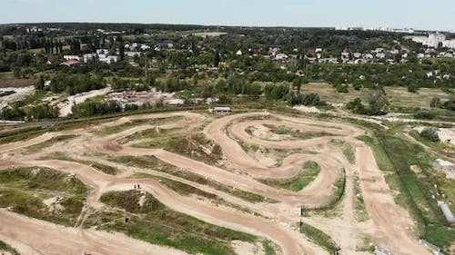 Motorcycle riders ride on sandy ground in motocross professional racetrack.