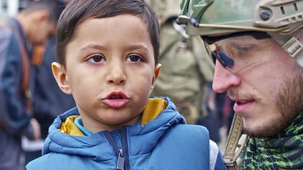 Thumbnail for Syrian Refugee Boy Chatting with Cheerful Soldier
