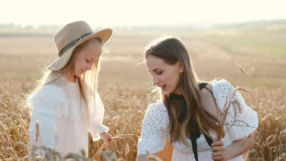 Thumbnail for Young Mother and Little Girl Picking Wheat in the Field