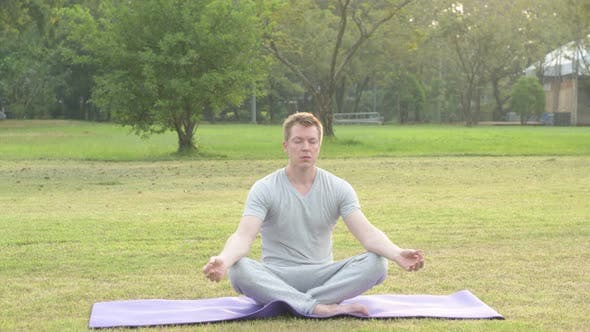 Thumbnail for Young Handsome Man Relaxing While Meditating at the Park