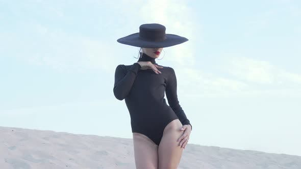 Thumbnail for Gorgeous Woman in Black Bodysuit and Hat Posing Gracefully Outdoors