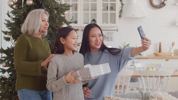 Thumbnail for Joyous Asian Family Taking Selfie with Smartphone near Christmas Tree