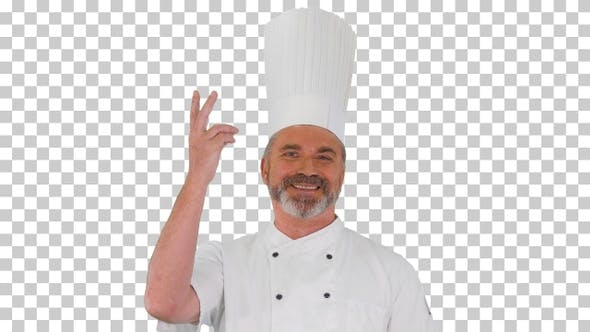 Male chef making real jam gesture to camera, Alpha Channel