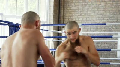 Rear View Shot of a Bearded Male Boxer Practicing in Front of the Mirror