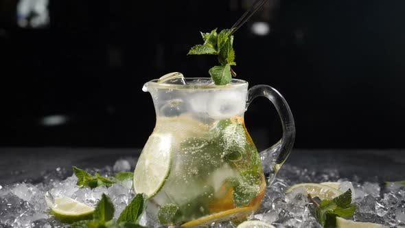 Summer Fresh Cocktail with Sparkling Water in Glass Jar with Sliced Lime Mint Leaves and Ice
