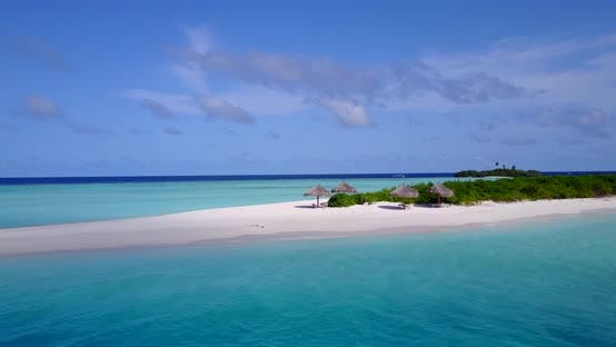Wide angle flying tourism shot of a sunshine white sandy paradise beach and blue water background in