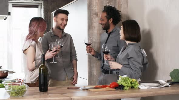 Thumbnail for Friends with Wine Glasses Chatting and Laughing in Kitchen