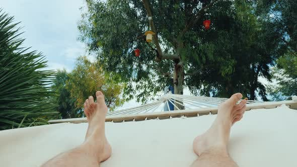 Thumbnail for Men's Feet Swinging in a Hammock. One on Vacation Concept