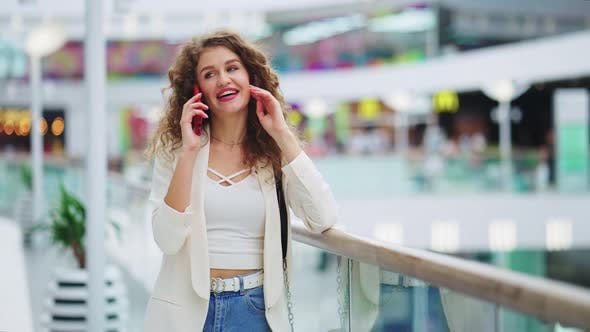 Cheerful Woman Talking on Phone in Mall