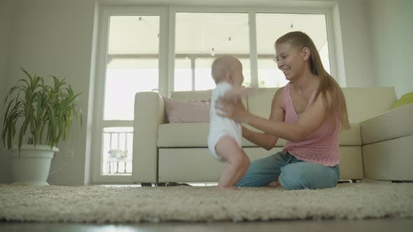 Thumbnail for Woman Teaches Her Little Child To Walk At Home In The Room