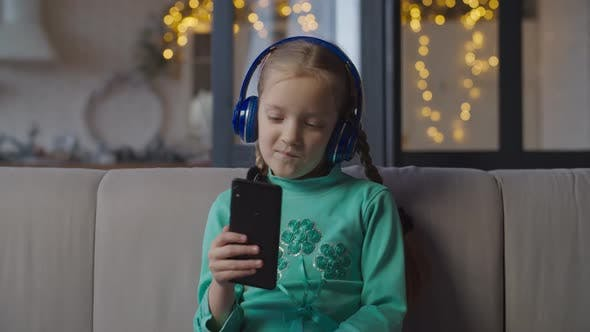 Cover Image for Girl in Headphones Listening To Music on Cellphone