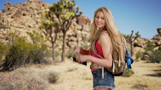 Thumbnail for Lovely young adult female hiking Joshua Tree park in spring