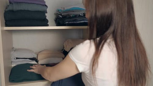 Housewife Organizing Clothes in Wardrobe.