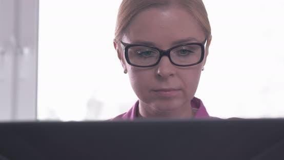 Thumbnail for Porträt der lächelnden Frau mit Brille arbeiten auf einem Laptop