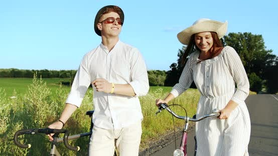 Thumbnail for Couple Walking with Bicycles on Field Road