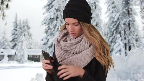 Thumbnail for Young Caucasian woman removes gloves to text on phone outside cabin in the snow