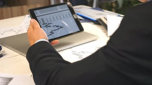 Male Hands of Young Businessman Analyzing Statistical Data Information on a Tablet Pc and Drinking