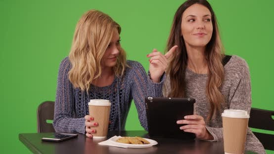 Thumbnail for Couple of joyful girls sitting and looking at tablet for chroma key compositing