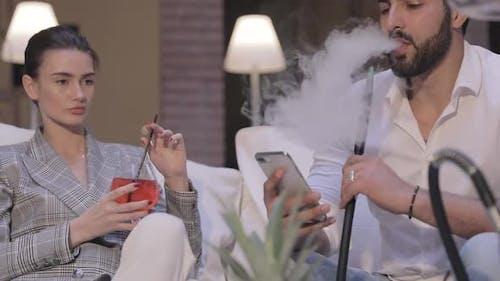 Couple At Shisha Bar. Man Smoking Hookah And Using Phone
