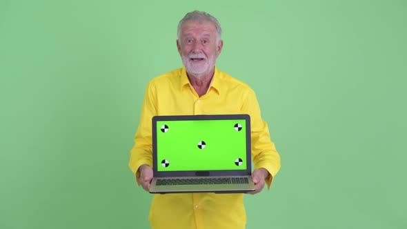 Cover Image for Happy Senior Bearded Businessman Showing Laptop and Looking Surprised