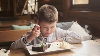 Appetite and enjoyment of food. Funny baby boy eating brownie. Child eats with appetite