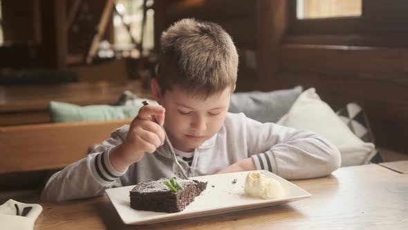 Appetit und Genuss von Essen. Lustiger kleiner Junge isst Brownie. Kind isst mit Appetit
