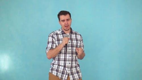Mittlerer Mann singt in ein Karaoke-Mikrofon