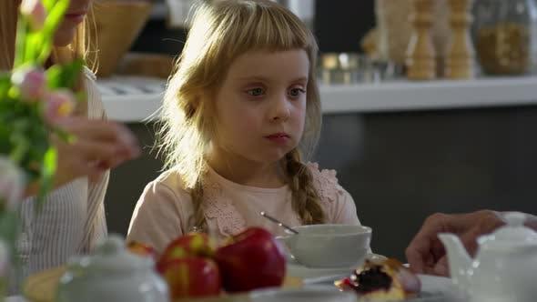 Thumbnail for Adorable Girl Enjoying Pie at Family Dinner