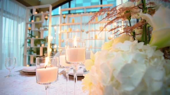 Thumbnail for Close-up View of Burning Candles in Transparent Glasses Standing on Banquet Table of Wedding Feast