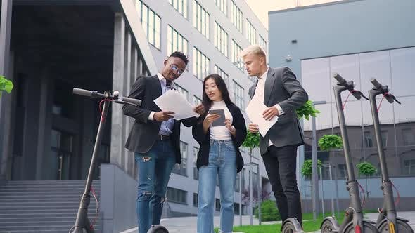 Thumbnail for Young Mixed Race People Standing Near Modern Building and Revisioning Financial Documents