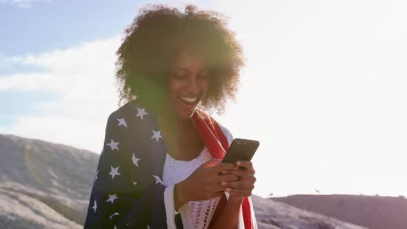 Woman wrapped with american flag and using mobile phone 4k
