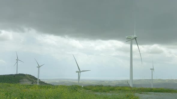 Thumbnail for Wind Turbines Spinning in Green Field Under Gray Stormy Sky, Bad Rainy Weather