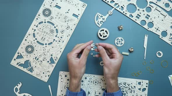 Man assembling flywheels and small pieces of wooden puzzle toy.