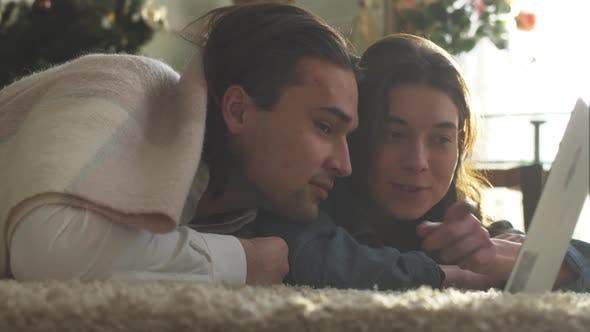 Thumbnail for Young Guy and Girl Covered with a Blanket Lying on the Floor Looking at Laptop at Home