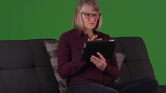 Lively elderly woman using portable tablet computer to browse on greenscreen