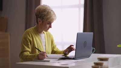 Elderly Female Accountant is Working at Home Office Remotely Work Mode for Old People During