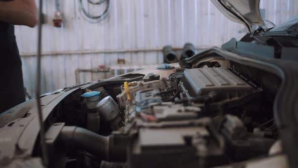 Auto Mechanic Pours Car Oil Into Car Engine