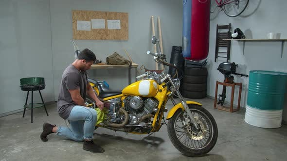 Thumbnail for Young Man Wipes a Motorcycle with a Rag in the Garage