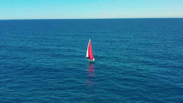 Thumbnail for Yacht Sailing on Open Sea at Sunny Day. Sailing Boat with a Red Sail