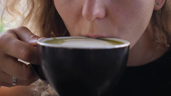 Thumbnail for Close Up of Girl Enjoying a Sip of Warm Cappuccino in Black Mug . Latte Art Concept
