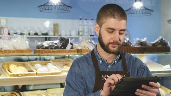 Thumbnail for Handsome professionelle männliche Bäcker mit digitalen Tablet in seinem Geschäft